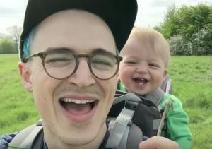 タンポポで笑う赤ちゃんとお父さん